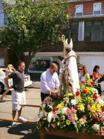 San Mauro stops throughout the procession for people to pin money on him.